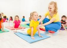 Petite fille faisant étirant l'exercice avec l'entraîneur Photos stock