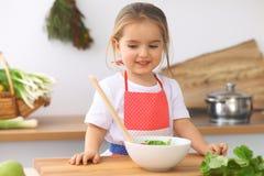 Petite fille faisant cuire dans la cuisine Tomates d'enfant et verdure de découpage en tranches et de mélange Concept de repas sa Photos stock