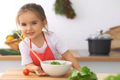 Petite fille faisant cuire dans la cuisine Tomates d'enfant et verdure de découpage en tranches et de mélange Concept de repas sa Image libre de droits