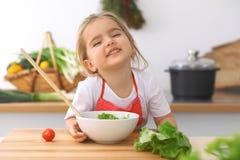 Petite fille faisant cuire dans la cuisine Tomates d'enfant et verdure de découpage en tranches et de mélange Concept de repas sa Image stock