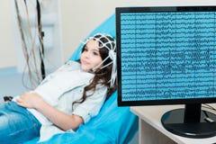 Petite fille faisant enregistrer ses ondes cérébrales par l'intermédiaire de l'électro-encéphalographe Photo libre de droits