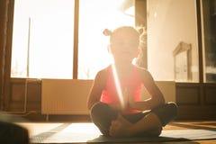 Petite fille faisant l'exercice à la maison image stock