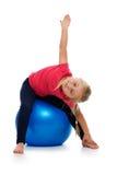 Petite fille faisant l'exercice de forme physique avec la bille de gymnastique. Photographie stock libre de droits