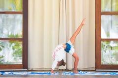 Petite fille faisant l'exercice de yoga sur la terrasse dehors Images libres de droits