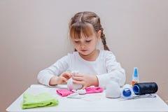 Petite fille faisant le bonhomme de neige de jouet à partir des chaussettes Photo libre de droits