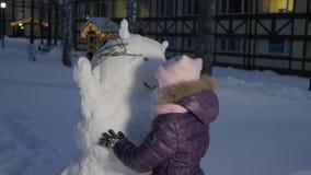 Petite fille faisant le bonhomme de neige et regardant là-dessus en parc neigeux banque de vidéos
