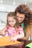 Petite fille faisant les formes de papier avec la mère à la table Photos stock