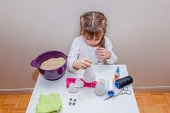 Petite fille faisant un bonhomme de neige de jouet elle-même Photos stock