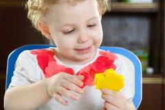 Petite fille faisant une forme d'étoile à partir de la pâte d'argile Photographie stock libre de droits