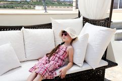 Petite fille fatiguée détendant sur le divan de terrasse Photographie stock