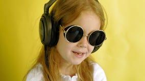 Petite fille gaie dans des écouteurs sur un fond jaune Verticale de plan rapproch? banque de vidéos