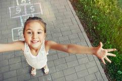 Petite fille gaie jouant le jeu de marelle sur le terrain de jeu Photo libre de droits