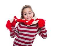 Petite fille gaie mignonne utilisant le chandail, l'écharpe barrée et les mitaines tricotés d'isolement sur le fond blanc Vêtemen Images stock