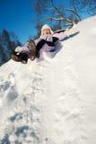 Petite fille glissant dans la neige image stock