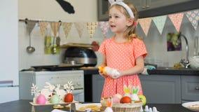 Petite fille goûtant crème pour des biscuits de Pâques banque de vidéos