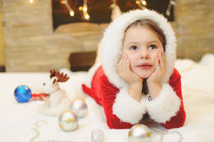 Petite fille habillée comme Santa par la cheminée Photographie stock libre de droits