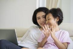 Petite fille heureuse à l'aide d'un ordinateur portable avec sa mère Photo stock