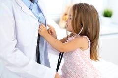 Petite fille heureuse à l'examen de santé au bureau de docteur Concept de médecine et de soins de santé photographie stock