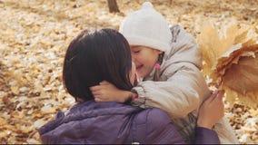 Petite fille heureuse étreignant sa mère en parc d'automne banque de vidéos