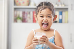 Petite fille heureuse après lait de consommation Photographie stock