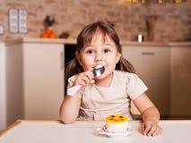 Petite fille heureuse avec la cuillère et le gâteau Photos libres de droits