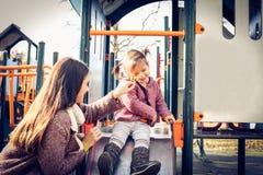 Petite fille heureuse avec la mère dans le terrain de jeu Photos libres de droits