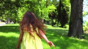 Petite fille heureuse avec la robe jaune fonctionnant nu-pieds sur l'herbe verte en parc banque de vidéos