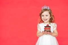 Petite fille heureuse avec le gâteau d'anniversaire d'isolement sur le fond rouge Photos libres de droits