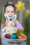 Petite fille heureuse avec le lapin de jouet et les oeufs de pâques photographie stock