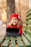 Petite fille heureuse avec le PC de comprimé sur le banc Photo stock