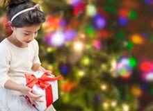 Petite fille heureuse avec le présent au-dessus des lumières Photographie stock libre de droits