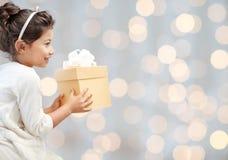 Petite fille heureuse avec le présent au-dessus des lumières Photos stock