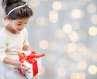 Petite fille heureuse avec le présent au-dessus des lumières Images stock