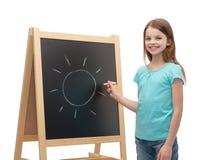 Petite fille heureuse avec le soleil dessiné sur le tableau noir photos stock