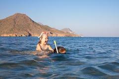 Petite fille heureuse avec les verres de plongée sur le dos de la femme naviguant au schnorchel dans l'eau d'une plage en Andalou photographie stock