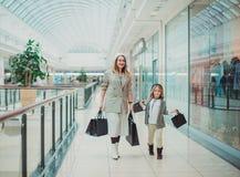 Petite fille heureuse avec sa maman dans le caddie et ses parents appréciant le week-end au grand centre commercial photo stock