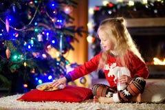 Petite fille heureuse ayant le lait et des biscuits par une cheminée dans un salon foncé confortable le réveillon de Noël Image stock