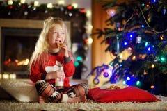 Petite fille heureuse ayant le lait et des biscuits par une cheminée dans un salon foncé confortable le réveillon de Noël Images libres de droits
