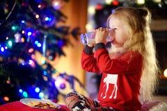 Petite fille heureuse ayant le lait et des biscuits par une cheminée dans un salon foncé confortable le réveillon de Noël Images stock