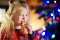 Petite fille heureuse ayant le lait et des biscuits par une cheminée dans un salon foncé confortable le réveillon de Noël Image libre de droits