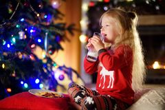 Petite fille heureuse ayant le lait et des biscuits par une cheminée dans un salon foncé confortable le réveillon de Noël Photos libres de droits