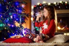 Petite fille heureuse ayant le lait et des biscuits par une cheminée dans un salon foncé confortable le réveillon de Noël Photo stock
