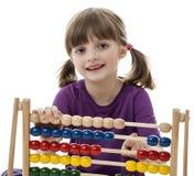 Petite fille heureuse comptant avec l'abaque Images libres de droits