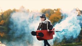 Petite fille heureuse d'aviateur courant le long du lac de coucher du soleil dans l'avion de carton d'amusement avec de la fumée  clips vidéos