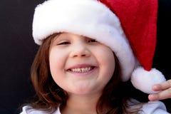 Petite fille heureuse dans le chapeau de Santa Image stock