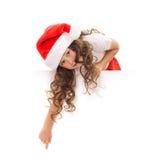 Petite fille heureuse dans le chapeau de Santa jetant un coup d'oeil par derrière Photos libres de droits