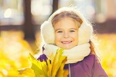 Petite fille heureuse dans les earflaps avec des feuilles d'automne Photographie stock