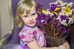 Petite fille heureuse de princesse dans la robe et la couronne roses dans sa pièce royale se reposant sur la chaise et tenant le  Images libres de droits