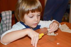Petite fille heureuse employant des ciseaux à la maison Images stock