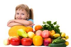 Petite fille heureuse et beaucoup de fruits et légumes Image stock